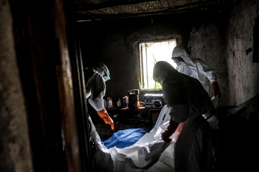 Health workers sterilize the house and prepare a body for burial in Lango village, Kenema, Sierra Leone. (Photo courtesy of Andalou Agency)
