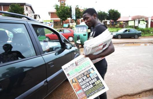 A newspaper vendor stands along road as he holds newspapers with a front page headline reading 'Chibok girls: We've reached deal with Boko Haram', in Abuja October 18, 2014. Credit:  EUTERS/Stringer